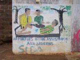 Anche sui muri del villaggio di Afagnan l'invito ad aiutare i malati di AIDS.